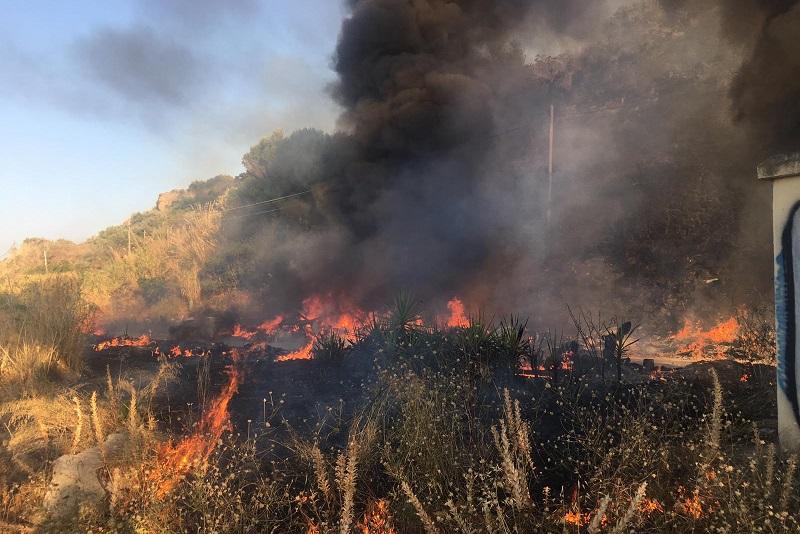 Sterpaglie e rifiuti in fiamme: densa colonna di fumo nero in cielo